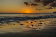 La puesta del sol en la playa de Fuerteventura con lava oscila Foto de archivo libre de regalías