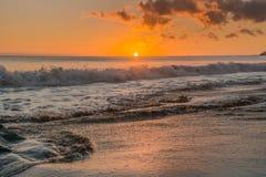 La puesta del sol en la playa de Fuerteventura con lava oscila Fotos de archivo