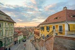 La puesta del sol en Sibiu contiene los tejados Imagen de archivo libre de regalías