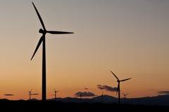 La puesta del sol en una granja de viento Imágenes de archivo libres de regalías