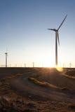 La puesta del sol en una granja de viento Imagen de archivo libre de regalías