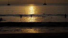 La puesta del sol hermosa con las siluetas de la gente goza del océano metrajes