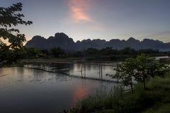 La puesta del sol hermosa con la nube colorida reflejó en el río y el puente de madera, Vang Vieng, Laos de Nam Song imagen de archivo libre de regalías