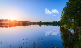 La puesta del sol hermosa del cielo en el agua Fotos de archivo