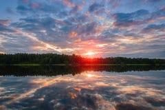 La puesta del sol hermosa del cielo en el agua Imagen de archivo libre de regalías