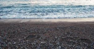 La puesta del sol hermosa en la opinión de la playa de la arena y del mar agita salpicar en vídeo perfecto del paisaje 4K de la n almacen de metraje de vídeo