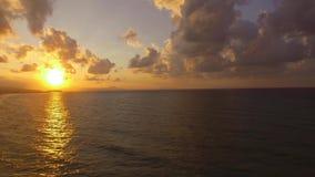 La puesta del sol hermosa sobre el mar con el cielo y las nubes rojos fue filmada con el abejón almacen de video