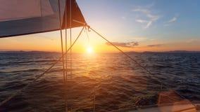 La puesta del sol imponente con la navegación navega en el mar lujo Foto de archivo libre de regalías