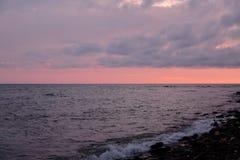 La puesta del sol, los rayos del ` s del sol hace su manera a través de las nubes pesadas e ilumina el verano, mar preocupado foto de archivo libre de regalías