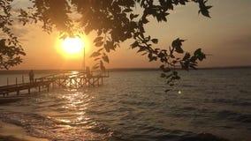 La puesta del sol del muelle en el mar agita luz del sol video reducida un pescador se está colocando en una pesca del muelle par almacen de metraje de vídeo