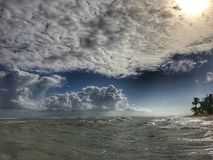 La puesta del sol del océano El sol poniente destaca algunas nubes de cúmulo con los rayos de oro Fotos de archivo libres de regalías