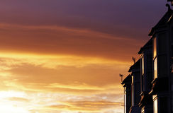 La puesta del sol reflejó en ventanas de la casa Foto de archivo libre de regalías