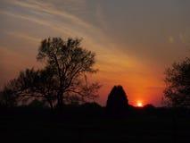 La puesta del sol roja en una zona rural, humo del incendio fuera de control hace el rojo del cielo Foto de archivo