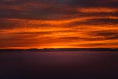 La puesta del sol roja se nubla con humo a través de fondos del océano Fotos de archivo