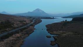 La puesta del sol sobre el soporte errigal y el lago Nacung bajan, condado Donegal - Irlanda almacen de video