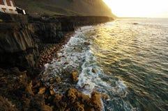 La puesta del sol sobre la orilla del océano Imágenes de archivo libres de regalías