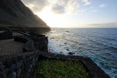 La puesta del sol sobre la orilla del océano Imagen de archivo