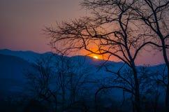 La puesta del sol sobre las montañas Imagen de archivo libre de regalías