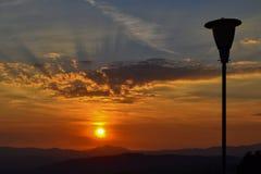 La puesta del sol sobre las montañas con una calle vieja aligera con el cielo azul y anaranjado y algunas nubes Fotografía de archivo