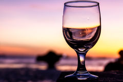 La puesta del sol tropical en la playa reflejó en una copa de vino, verano v Fotos de archivo libres de regalías