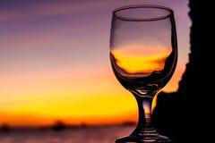 La puesta del sol tropical en la playa reflejó en una copa de vino, verano v Foto de archivo libre de regalías