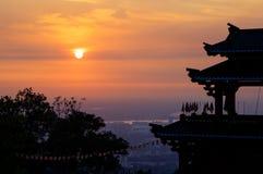 La puesta del sol va abajo en el tejado del templo imagenes de archivo