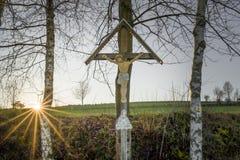 La puesta del sol y los rayos de sol pasados con una manera cruzan en el bosque bávaro Foto de archivo