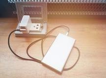 La puissance de remplissage encaissent le connecteur, sur une table en bois brune et vident avec l'espace de copie pour le texte images libres de droits