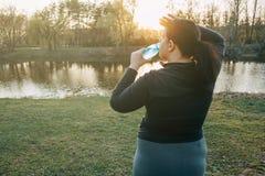 La pulitura di peso eccessivo della donna ha sudato ed acqua potabile Immagine Stock Libera da Diritti