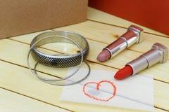La pulsera y el lápiz labial con el corazón forman símbolo dibujado en un pedazo de Libro Blanco en la tabla de madera Imagen de archivo libre de regalías