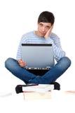 La pupila aprende frustrado con los libros y la computadora portátil Imágenes de archivo libres de regalías