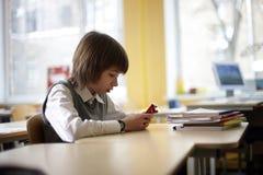 La pupila de la escuela se sienta en la escuela con el teléfono celular Foto de archivo