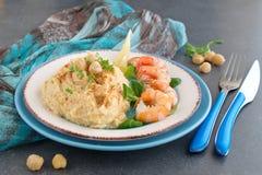 La purée de pois chiche avec de la crème et le beurre a servi avec les crevettes roses bouillies d'un plat blanc et bleu sur un f photo libre de droits
