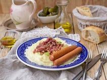 La purée de pommes de terre avec des pommes a servi avec les saucisses et le lard Photographie stock libre de droits