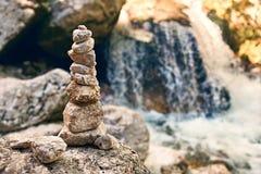 La pyramide des pierres de zen sur les montagnes rocheuses coulent le rivage images libres de droits