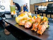 La quemadura del camarón del sushi el sushi de color salmón de la gamba y de Aburi de río de Aburi del fuego con la salsa y Tamag imagen de archivo