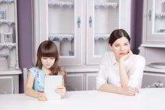 La querelle de mère et de fille en raison de l'abus le comprimé téléphonent l'ordinateur, le comprimé, etc. Images stock