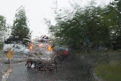 La queue de voiture s'allume par un pare-brise couvert par pluie, foyer sur des baisses de pluie Photo libre de droits