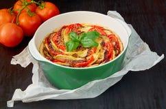 La quiche francesa tradicional del plato con las berenjenas y los tomates en el plato de la hornada adornado con albahaca fresca  imágenes de archivo libres de regalías