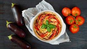 La quiche francesa tradicional del plato con las berenjenas y los tomates en el plato de la hornada adornado con albahaca fresca  imagenes de archivo