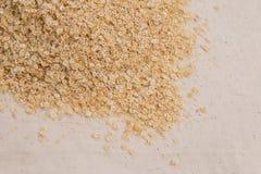 La quinoa si sfalda in un angolo del telaio su tessuto pallido Immagine Stock Libera da Diritti