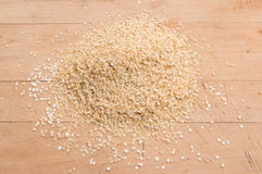 La quinoa si sfalda in un mucchio su un bordo di legno Fotografia Stock