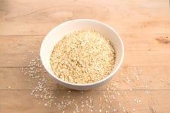 La quinoa si sfalda in una ciotola di miscelazione su un bordo di legno Fotografia Stock Libera da Diritti