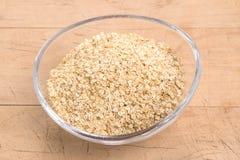 La quinoa si sfalda in una ciotola di vetro ovale su un fondo crema l Immagine Stock