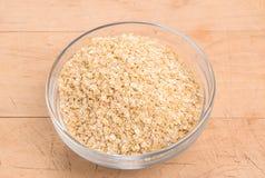 La quinoa si sfalda in una ciotola di vetro rotonda su legno Fotografia Stock