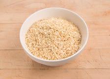 La quinoa si sfalda in una ciotola di vetro rotonda su legno Immagine Stock