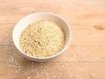 La quinoa si sfalda in una ciotola di vetro rotonda su legno Fotografia Stock Libera da Diritti