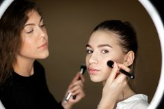 La réflexion dans le miroir du maquilleur la fille avec du charme fait le maquillage à une belle jeune fille image stock