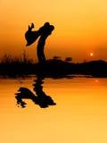 La réflexion de l'homme et la femme aiment la silhouette dans le coucher du soleil Photos stock