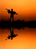 La réflexion de l'homme et la femme aiment la silhouette dans le coucher du soleil Photo stock
